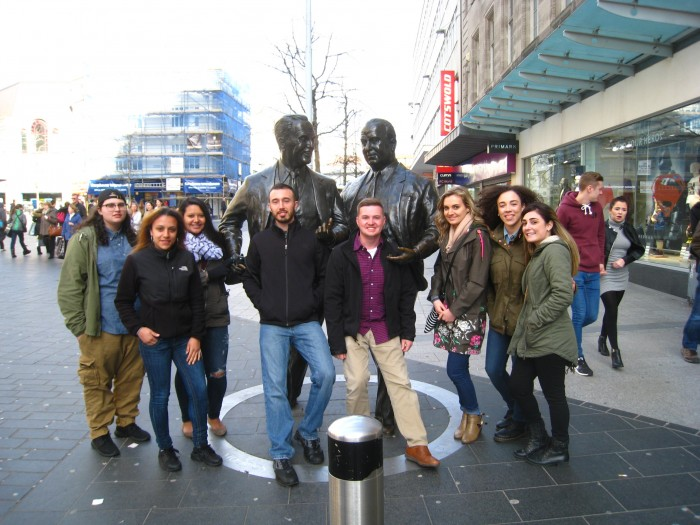 Southern students stand in front of the John Moores statue on the streets of Liverpool.