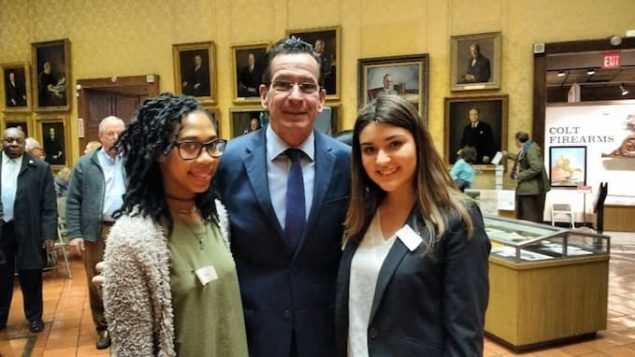 Journalism majors Adrianna Rochester, left, of Hartford, and Sandra Gomez-Aceves, right, of Meriden, with Connecticut Gov. Dannel P. Malloy Thursday following a ceremony commemorating Connecticut's involvement in World War I 100 years ago on April 6, 1917.