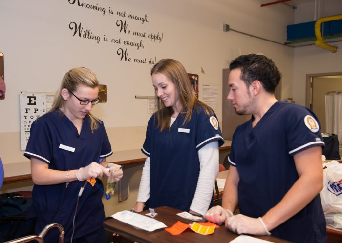 Three SCSU nursing students working together in nursing lab