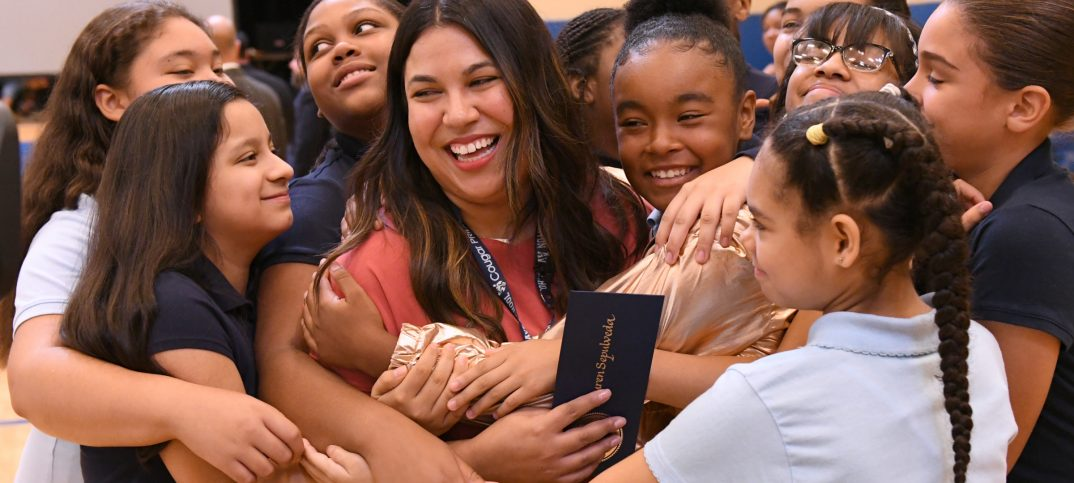 A group of students come in for a group hug to support their award-winning teacher.
