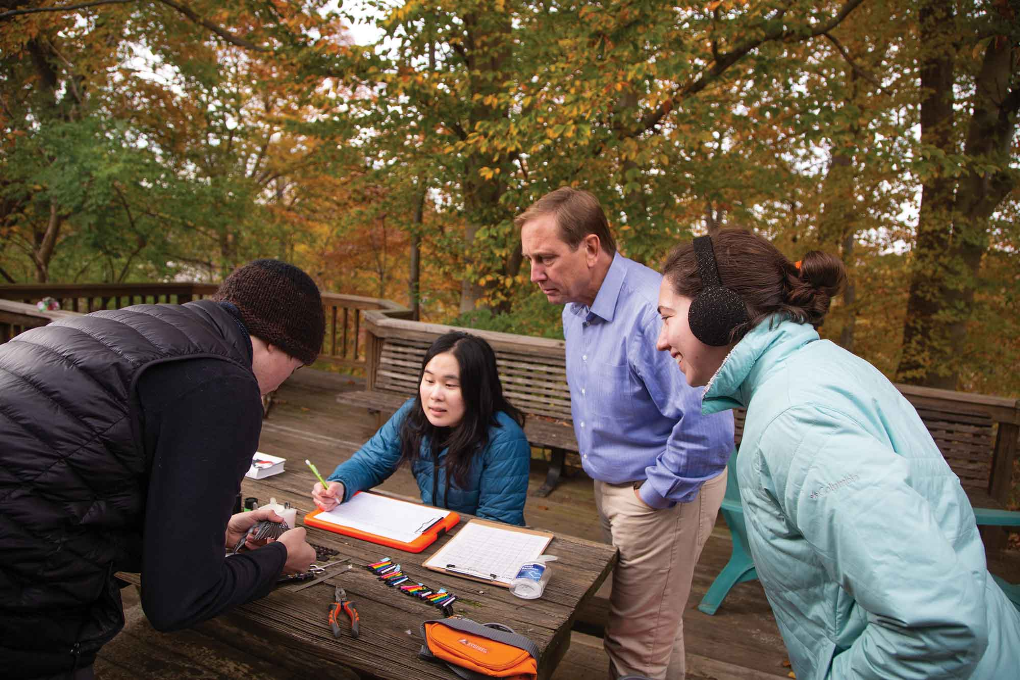 SCSU alumnus Peter Marra, '85, with students observing bird, writing in journal
