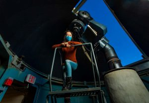 a student prepares to use the telescope inside the campus observatory