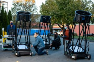 Physics Professor Elliott Horch and students use portable telescopes outside