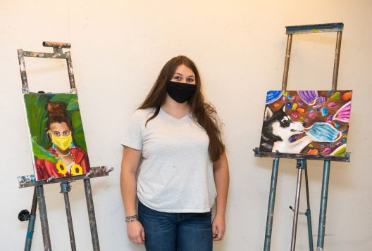 portrait of SCSU student artist Isabelle Reina with her work