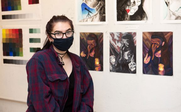 portrait of SCSU student artist Jaime Roy with her work