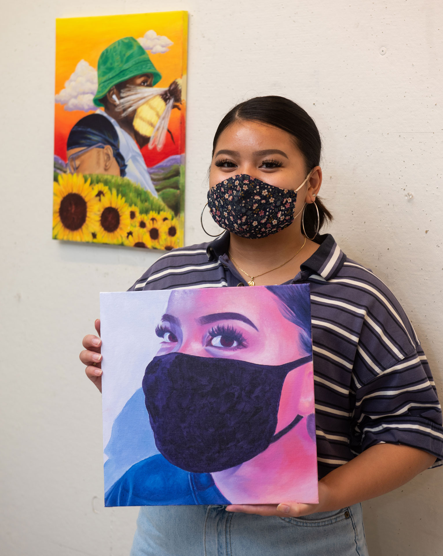 portrait of SCSU student artist Kyra Catubig with her work
