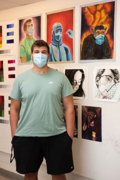 portrait of SCSU student artist Nathan Shilling with his work