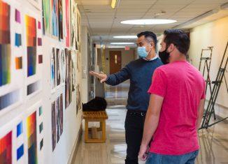 SCSU art professor Thuan Vu reviewing student artwork in Earl Hall