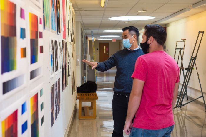 SCSU art professor Thuan Vu reviewing student artwork in Earl Hall