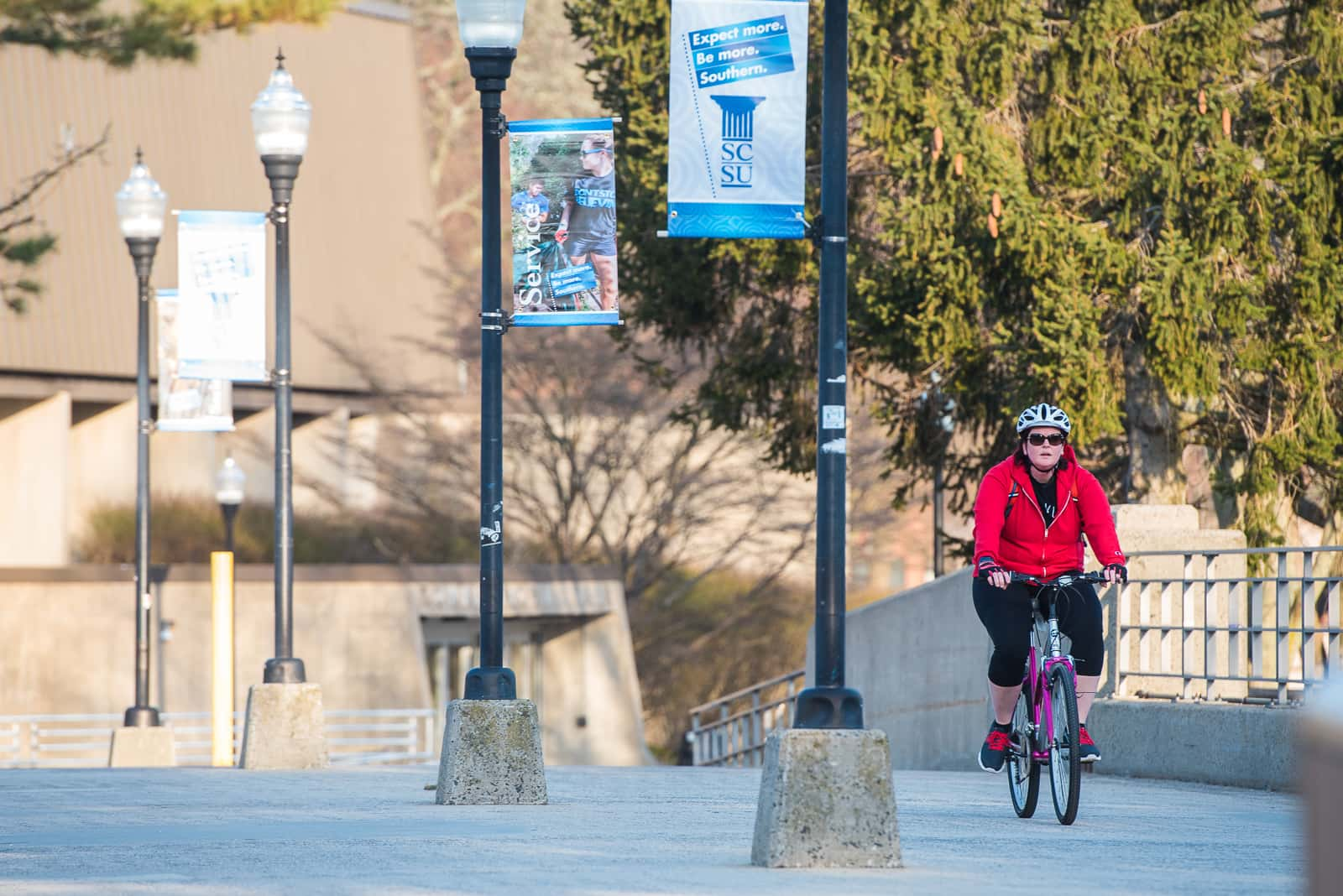 a student rides a bike across the Fitch St footbridge