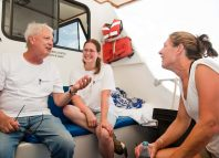 Jim Tait and two students sit on a boat and talk