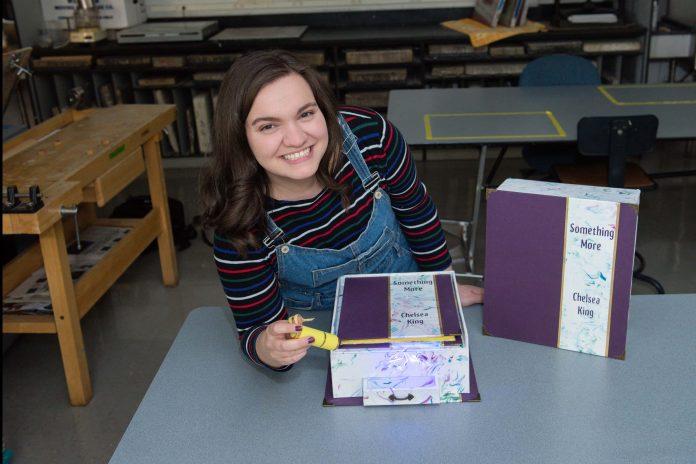Chelsea King displays her book