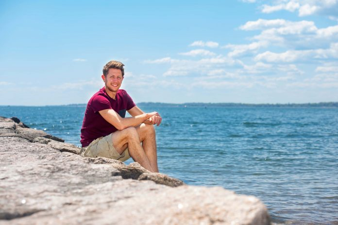 Louie Krak sits on rocks near Long Island Sound