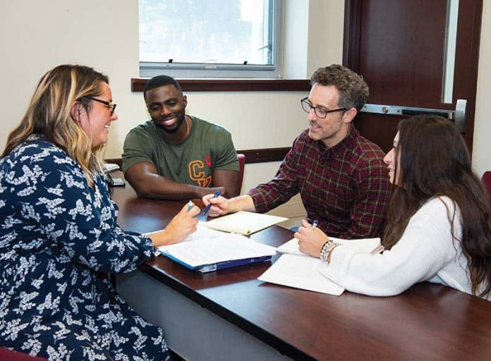 four graduate students sit around a table looking at books together
