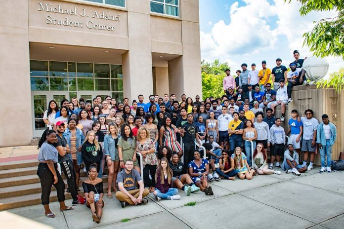 a large group of students standing on the steps of the Adanti Student Center