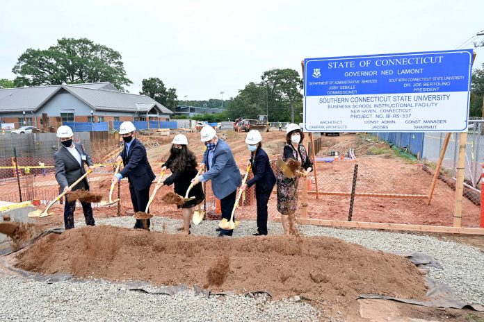 Breaking ground (left to right): someone from the State Department of real Estate & Construction Services; Garrett Sheehan, president and CEO, Greater New Haven Chamber of Commerce; Mariam Noorzad, '21; President Joe Bertolino; Jennifer Robin, dean of the School of Business; and Ellen Durnin, dean emerita of the School of Business