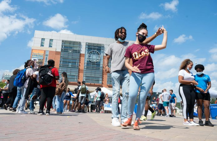 Two students dance together on Buley Plaza with groups of students in the background